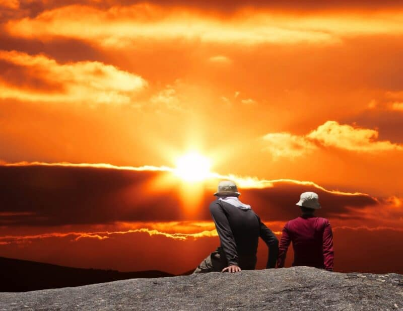 couple at sunset at edge of mountain