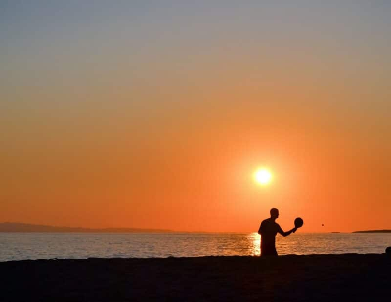 person playing in sand at sunset